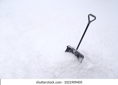 Snow Shovel in Snow Pile During Cold Winter White Snowstorm