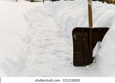 Snow shovel in the snowdrift. Cleaning footpaths.