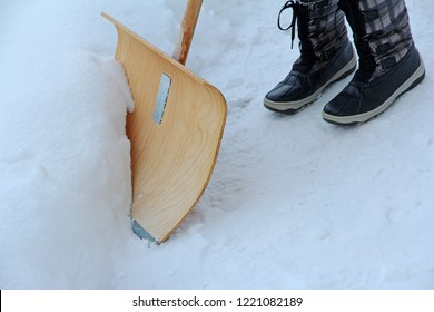 Snow shovels in winter. A woman shovels the snow away with a snow shovel.