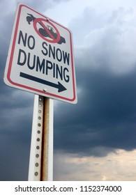 """""""No Snow Dumping"""" sign set against a dark, stormy sky."""