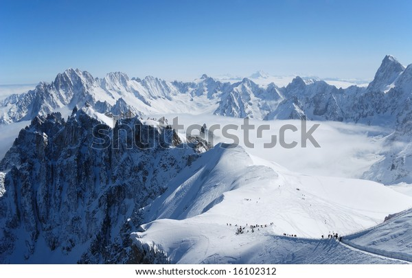 Snow slope with mountain-skiers against blue sky and steep peaks of the Alps, Mont Blanc, France