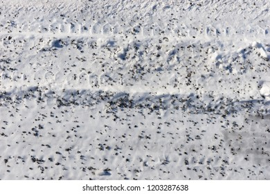 Snow with small pebbles on the street. Winter background