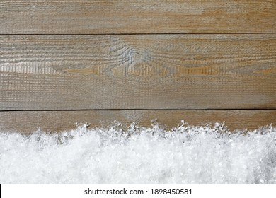 Snow and space for text on wooden background, top view. Christmas time