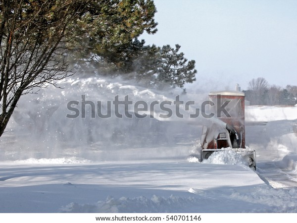 Snow thrower blowing snow with garden tractor rural plowing snow removal Winter stream of snow.