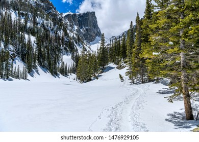 Snow Trail - A snow hiking trail winding along side of froze Dream Lake towards towering Hallett Peak. Rocky Mountain National Park, Colorado, USA.
