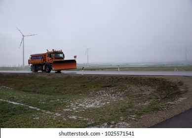 Snow truck on the road without snow and with wind turbines in the background
