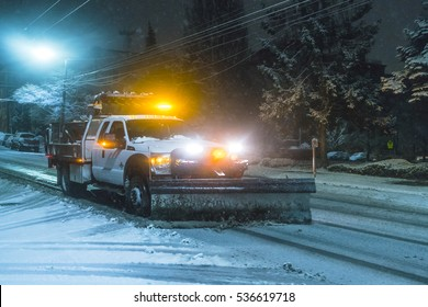 snow truck working at night on snowy day in downtown.