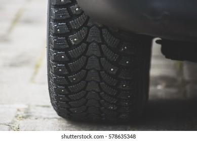 Snow tyre on pavement. - Shutterstock ID 578635348