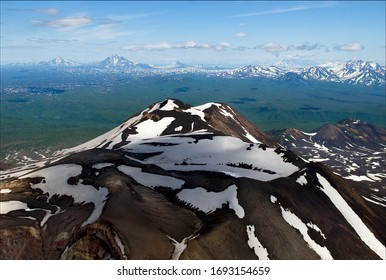 Snow volcanic mountain in Kamchatka peninsula, Russia from helicopter. Snow mountain peaks landscape of Kamchatka peninsula from above