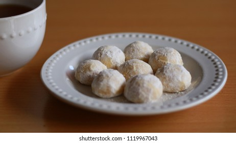 Snow White Cookies or Puteri Salju and a cup of tea with wood background.