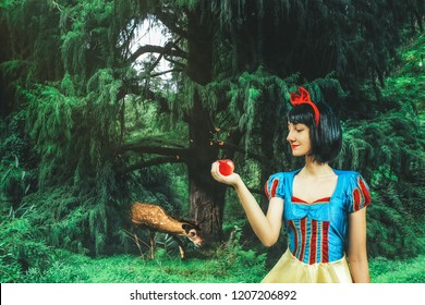 Snow White cosplay girl in the mysterious forest. Artistic processing
