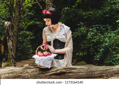 Snow White is in the forest, holding and looking to a red apple next to a basket full of apples.