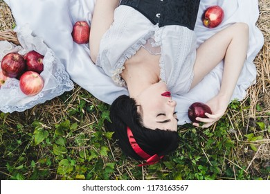 Snow White is laying in the floor in a deep sleep, surrounded by red apples.