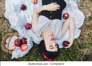 Snow White is laying in the floor, surrounded by red apples. She seems to be in a profound sleep.