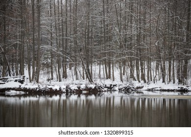 Snow white Winter reflections on Holiday Lake in Manalapan New Jersey.