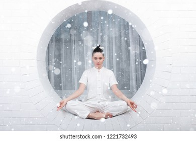 snow, winter, christmas, fitness, sport, training, lifestyle concept - Young woman doing yoga exercise. Portrait of young beautiful girl in white sportswear doing yoga practice over snow background