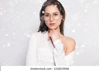 snow, winter, christmas, people, beauty concept- Pretty young girl in white blank t-shirt, wearing glasses, empty wall, studio portrait. Smiling brunette woman in eyeglasses over snow background