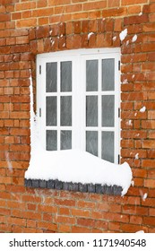 Snow in winter covers the window of an old brick house in England
