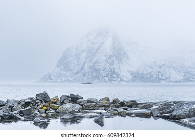 Snow winter mountains in fog. Large stones in the foreground. Norway landscape, Lofoten islands