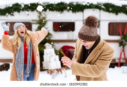 Snowball Fight. Romantic couple having fun outdoors, throwing snow at each other and laughing during winter camping with caravan, copy space
