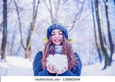 Snowball Fights. Little beautiful child girl having fun in snow. Fine winter day. (Christmas, happy childhood, new year, celebration concept)