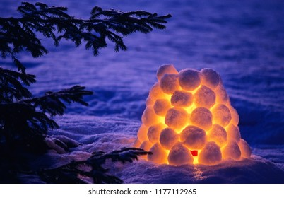 Snowball lantern beside spruce tree branches at dusk.