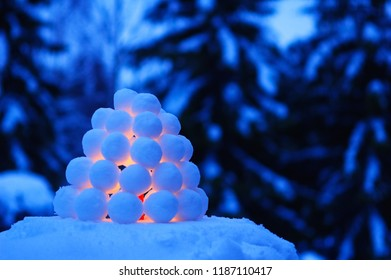 Snowball lantern in winter landscape at dusk.