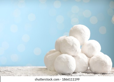 Snowballs on table against blurred lights, space for text