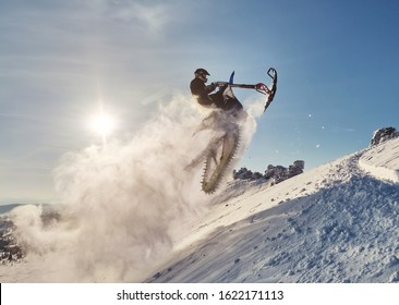 Snowbike rider in mountain valley in beautiful snow powder. Modify dirt bike with snow splashes and trail. Snowmobile sport riding, winter sunny day