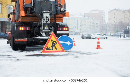 Snowblower clear freezing winter road with snow and ice.Snow-plow removes ice from the city street.Warning road sign and orange cone
