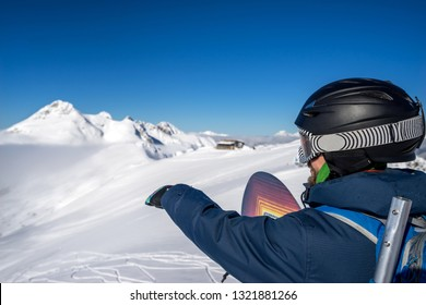 Snowboard Freerider points to the snow field to descend from the top of Caucasus mountains in winter resort of Krasnaya Polyana