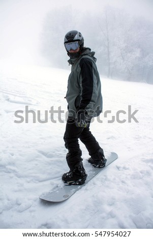 6f93b33e2d7 Snowboard. A man on a snowboard in a mask with no identification signs.  People