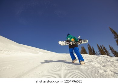 Snowboard man walking to mountain top with board. Winter sport holiday mountains sky resort