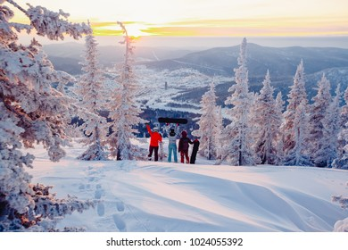 Snowboard. Team of girls' people watching sunrise surrounded by snow and fir trees, mountains. Concept travel, ski resort Sheregesh
