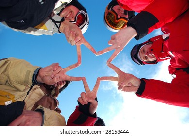 Snowboard team making a finger star in the blue ski as background