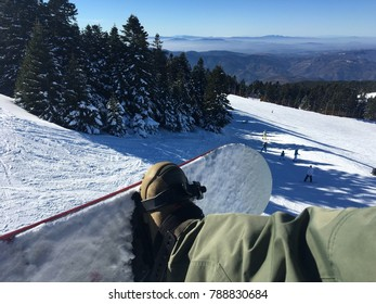 Snowboard from the viewpoint of my own perspective with snowy trees, mountain background