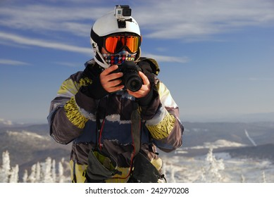 Snowboarder with action camera on helmet and SLR camera in his hands