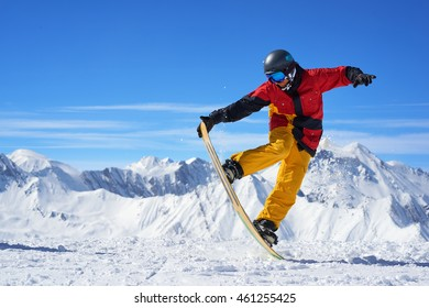 Snowboarder in bright sportswear doing balance trick against of beautiful mountains