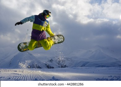 snowboarder does the jumping trick. snow scatters pieces of mountains in the background.