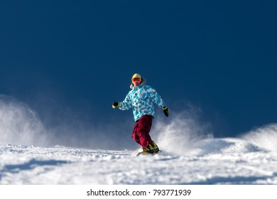 Snowboarder downhill at ski slope against blue sky