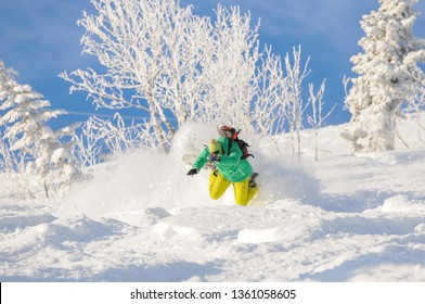 A snowboarder falling into deep snow at the ski resort in a sunny morning