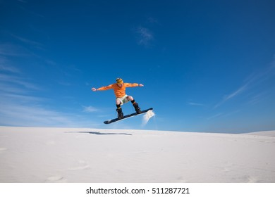 Snowboarder is flying over the sand dune. Snowboarding training in summer season. Sand boarding in desert.