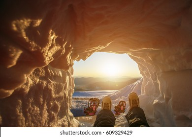 Snowboarder foot, having rest in snow cave on the top of mountain with sunrise view