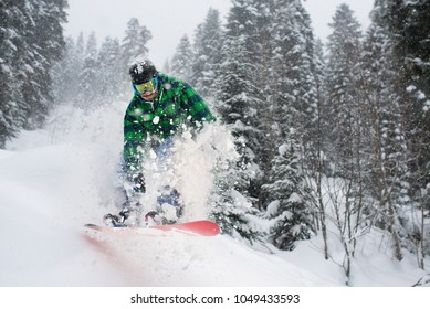 snowboarder in the forest jumping creating snow splashes