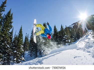 Snowboarder freerider jumping from a snow ramp in the sun on a background of forest and mountains.