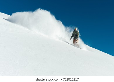 snowboarder in gear brakes on the slope freeride brakes creating a wave of snow