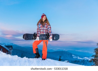 snowboarder girl holding a snowboard standing on a background of snowy mountains