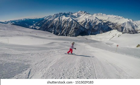 A snowboarder going down the slope in Heiligenblut, Austria. Perfectly groomed slopes. High mountains surrounding the girl, wearing pink trousers and colorful jacket. Girl wears helm for protection