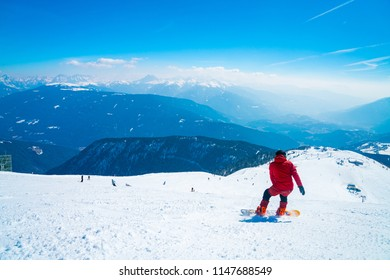 Snowboarder going down the slopes in Austrian Alps through forests, slopes and ski tracks. Skiing, snowboarding in the Alps.