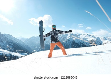 snowboarder holding a snowboard in his hands, standing in the snow, a clear day. snow mountains,